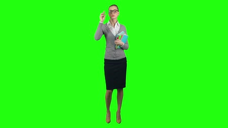 profesor : Strict female teacher isolated on green screen background standing with pile of note pads and looking at camera