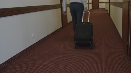bagagem : Rear view of businessman walking through the corridor in hotel with luggage