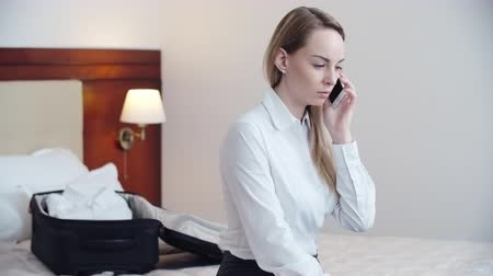 sitting room : Beautiful young businesswoman sitting on bed in hotel room and talking on the phone