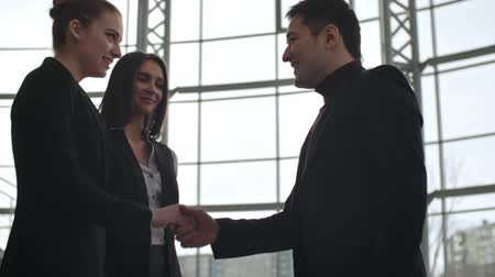 homem de negócios : Young Asian businessman greeting his female colleagues with handshake before meeting in business center, slow motion shot on Sony NEX 700
