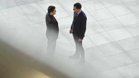 irodaház : Two young businessmen meeting in lobby of business center, shaking hands and talking; high angle view, slow motion shot on Sony NEX 700