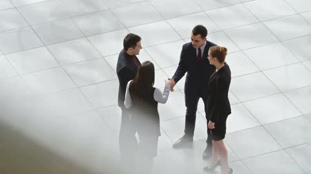 irodaház : High angle view of business partners meeting in lobby of business center, shaking hands and talking, shot on Sony NEX 700