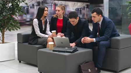lobi : Two young businesswomen chatting and two businessmen discussing work while sitting on leather sofa in lobby of office center, shot on Sony NEX 700 Stok Video
