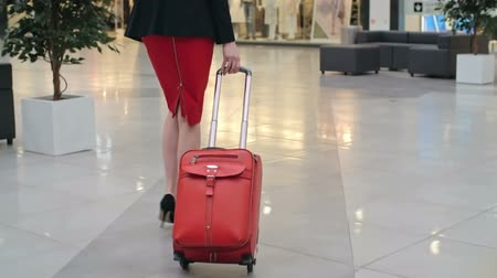 podróżnik : Rear view of elegant businesswoman pulling red suitcase across duty free zone at airport, slow motion shot on Sony NEX 700