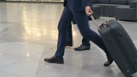 bagagem : Legs of two businessmen walking on tile flooring across terminal at airport, one of them pulling suitcase; tracking slow motion shot on Sony NEX 700