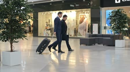 bagagem : Two young Asian businessmen walking across duty free zone at airport, one of them pulling suitcase, another man checking time; slow motion shot on Sony NEX 700