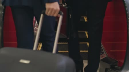 bagagem : Low section of two business travelers with suitcase going up escalator at airport, slow motion shot on Sony NEX 700