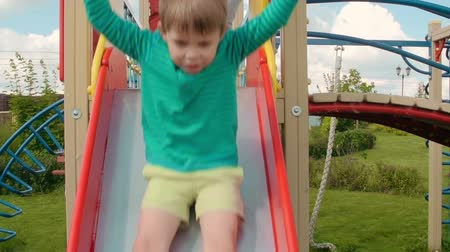 napfény : Kids riding down slide on playground and running on green grass in slow motion Stock mozgókép