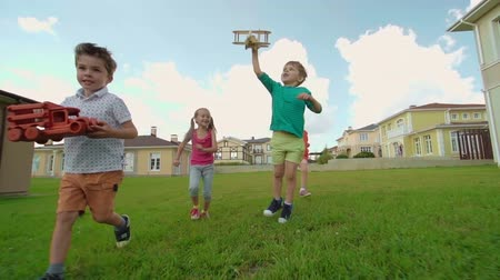 despreocupado : Four carefree kids running through green lawn: boys holding wooden airplane and car and two cute girls running behind them Stock Footage