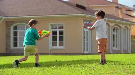 quintal : Two excited little boys playing with water guns on green lawn in the backyard in slow motion Vídeos