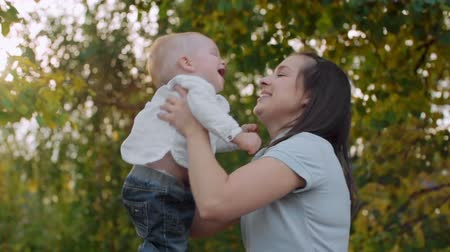 smile : Happy mother lifting her baby son up and spinning him in the park in slow motion