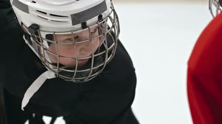 sporty zimowe : Close up of little hockey player in helmet standing face to face with his opponent and looking at him