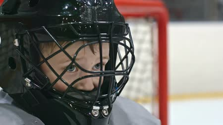 preparing : Close up of little boy in hockey uniform putting on his helmet and looking in front of him Stock Footage