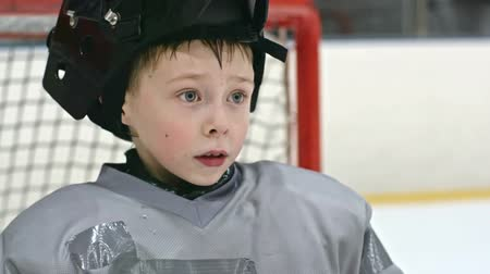 suor : Close up of little boy in hockey uniform taking off his helmet and drinking water from plastic bottle Vídeos