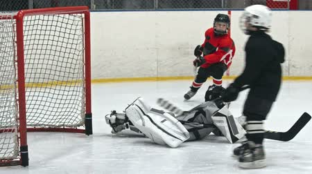 hockey rink : Little goaltender trying to prevent the opposing team from scoring but falling down on ice rink Stock Footage