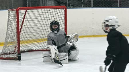 helmets : Child playing the position of goalie on an ice hockey team and protecting net from opposing team Stock Footage