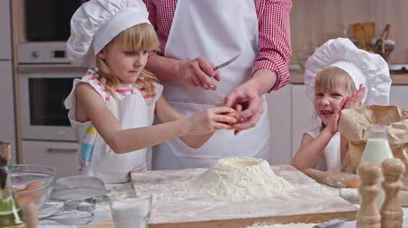 kötény : Little girl in chef hat and apron helping her dad to make dough: she adding egg to flour and her joyous sister clapping hands Stock mozgókép