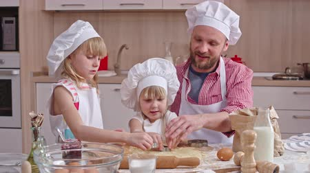 мучной : Lovely family spending their leisure time in the kitchen: dad and two little daughters enjoying cutting out cookies from dough together