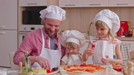 salame : Dad giving slices of tomato and ham to his daughters and girls putting them on pizza dough