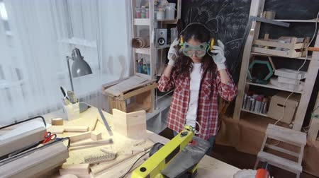kutilství : Young Asian craftswoman using planer machine to cut wood in her small woodworking studio