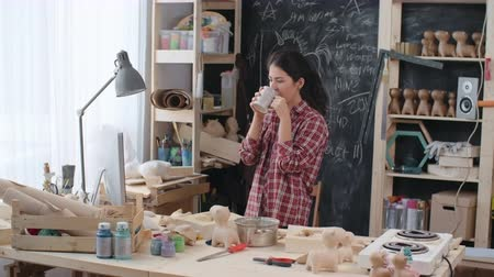kötény : Locked-down shot of young female Asian artist drinking tea, using computer and putting on work apron at her handmade studio dealing with production of paper mache toys