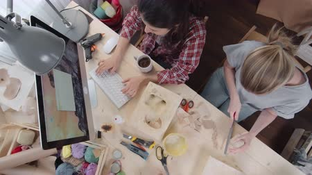 kutilství : Crane high angle view of two young female small business owners sitting at wooden table in craft studio, one of them using rasp for shaping handmade papier mache animal toy, another typing on computer