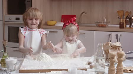fırınlama : Cute little sisters having fun in the kitchen: they tossing baking flour in the air and playing with it