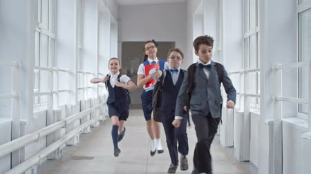 kinderen school : Vier schoolkinderen in uniform loopt naar de camera via de school corridor in slow motion