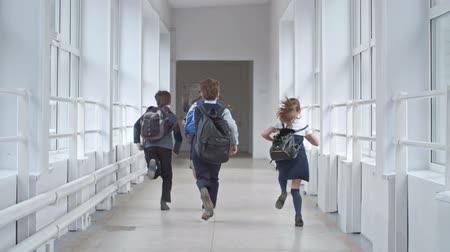 educar : Rear view of boys and girls with backpacks running through school corridor in slow motion Stock Footage