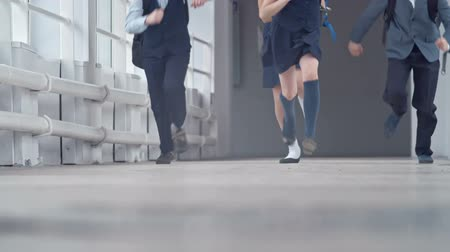 бросаясь : Close up of legs of school children running on the floor of corridor in slow motion
