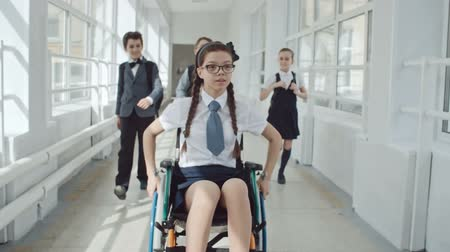 rokkant : Disabled girl riding wheelchair at school while her friends running through corridor to help her
