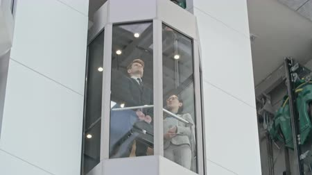 лифт : Businessman and businesswoman standing in glass elevator moving down