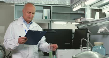 описание : Senior chemist standing in laboratory, looking at two different chemical substances in glass tubes and writing down description of them Стоковые видеозаписи