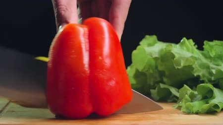 culinary : Close up of male hands cutting red bell pepper into two parts on wooden cutting board Stock Footage