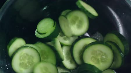 okurka : Close up of slices of cucumber falling into glass bowl Dostupné videozáznamy