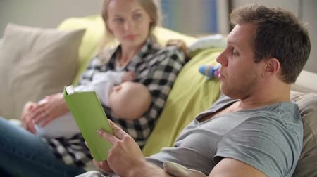 newborn child : Father reading aloud fairytale to his wife and newborn son on her hands