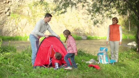 Father setting up a camp for whole family on the riverbank 影像素材