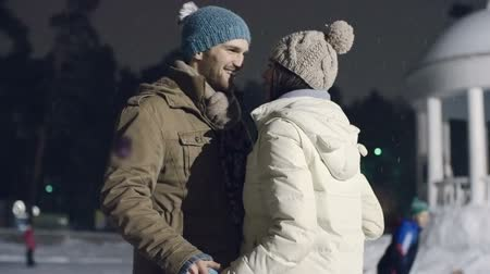 atividades : Beautiful loving couple embracing and kissing at outdoor ice skating rink during romantic winter date