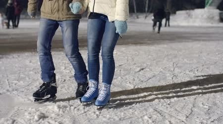 atividades : Tilt up shot of charming smiling couple ice skating together at outdoor rink in park Stock Footage