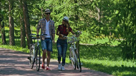 etkinlik : Beautiful young couple talking lively while walking with bikes through park in summertime