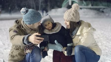 sporty zimowe : Joyous young family of three taking some happy selfies at outdoor skating rink in falling snow