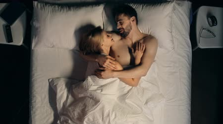 casal heterossexual : High angle view of charming young couple embracing in bed with white bedding, talking and laughing before sleep