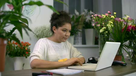 proprietário : Young Asian flower shop owner ordering wholesale flowers online Vídeos