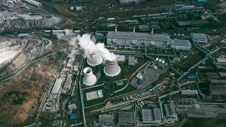 район : Aerial shot ofpower plant with cooling towersrejecting waste heat to atmosphere and producing steam surrounded by factoriesin large industrial area
