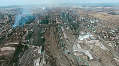 район : Panning aerial shot of large industrial area consisting of power plantsand factorieswith smoke coming out of chimneys and steam going out of cooling towers