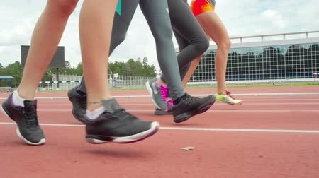 Legs of four female athletes running on track in slow motion, tracking shot Wideo