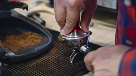 presleme : Closeup of coffee shop barista using tamper to press freshly ground coffee in portafilter, slow motion shot on Sony NEX 700