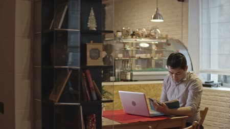 small businessman : Young Asian businessman sitting at table in cafe and making notes in personal organizer Stock Footage