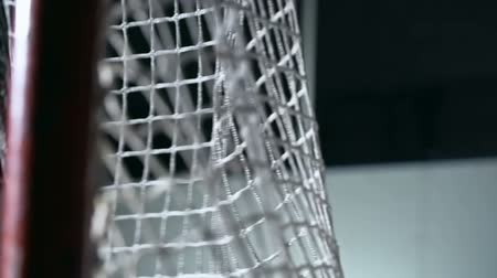 hockey rink : Close-up shot of hockey puck flying intogoal and hitting net in slow motion Stock Footage