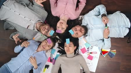 toco : Directly above view of young team with sticky notes on their foreheads lying on floor in circle and playing Who am I game, shot on Sony NEX 700 + Odyssey 7Q Vídeos
